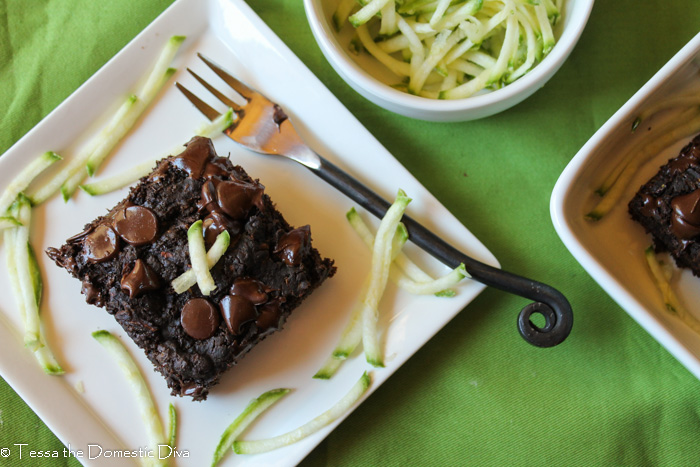 overhead shot of of a square of dark chocolate zucchini cake on white plate with shreds of fresh zucchini scattered on top of a green cloth