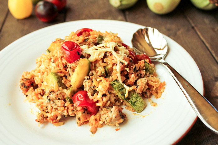white plate filled with a hot zucchini, cheese, tomato and rice casserole on a dark wooden surface