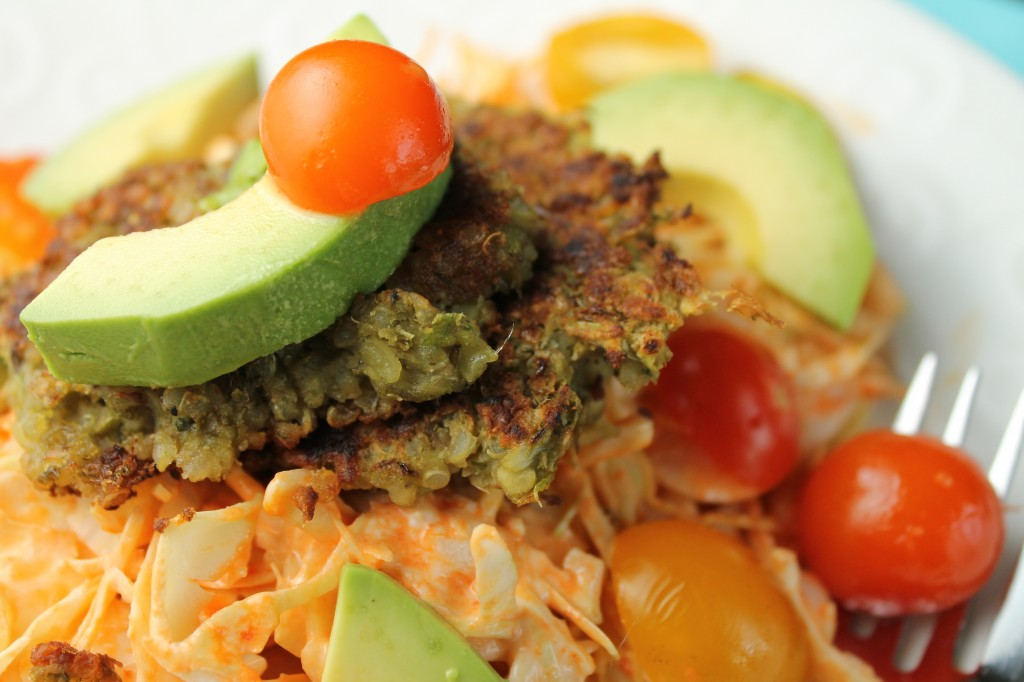 close up of quinoa and mung bean falafels topped with fresh avocado and cherry tomatoes