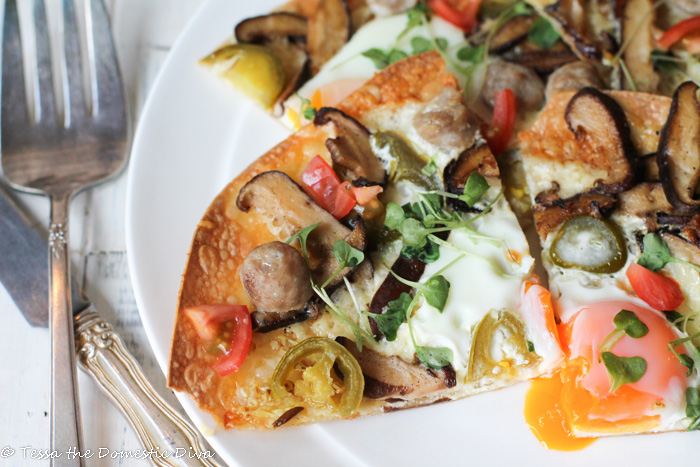 slices of a breakfast egg pizza with veggies atop a white plate from overhead