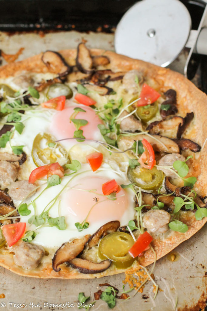 from the fron view of a crispy brown rice tortilla topped with fresh veggies, molten eggs atop a worn cookie sheet