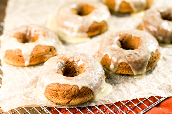 horizontal image of baked glazed pumpkin donuts atop a cooling rack