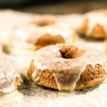 horizontal picture of glazed pumpkin donuts at eye level atop a piece of parchment paper