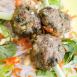 overhead view of three meatballs with cilantro, shredded carrots, chopped nuts, and lemongrass skewers