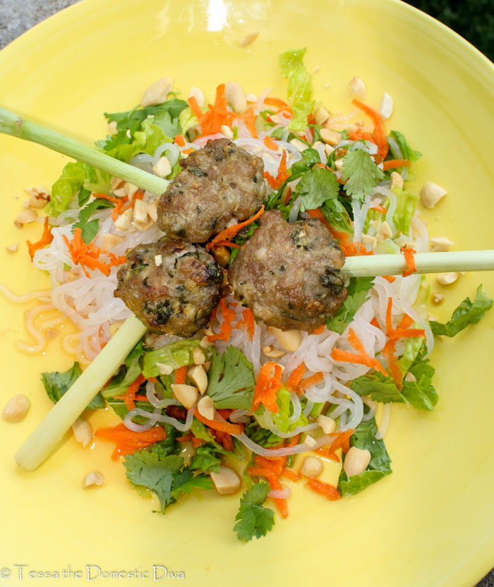 birds eye view of a a yellow plate with glass noodles, cilantro, carrots, and roasted meatballs