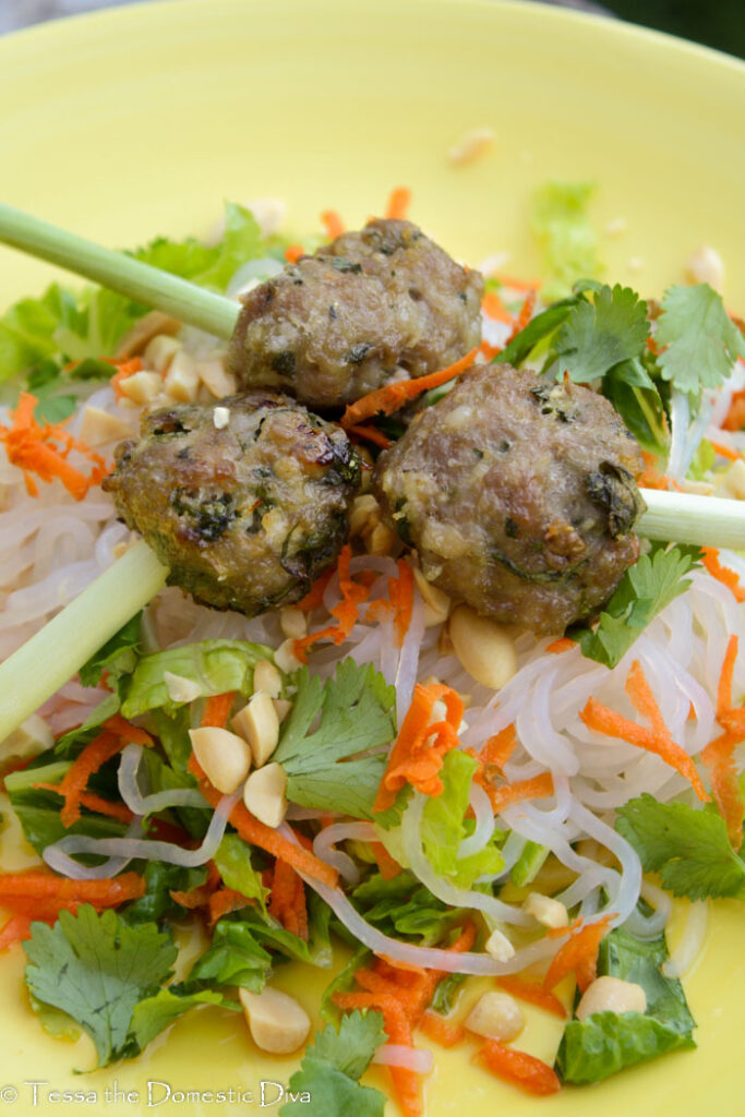 front view of three vietnamese pork meatballs with a lemongrass skewer atop noodles and veggies
