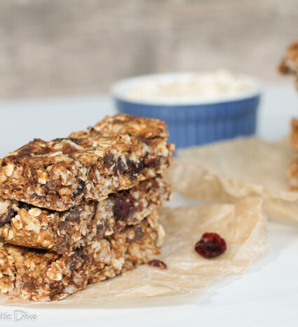 three stacked homemade granola bars on a parchment paper with cranberries.