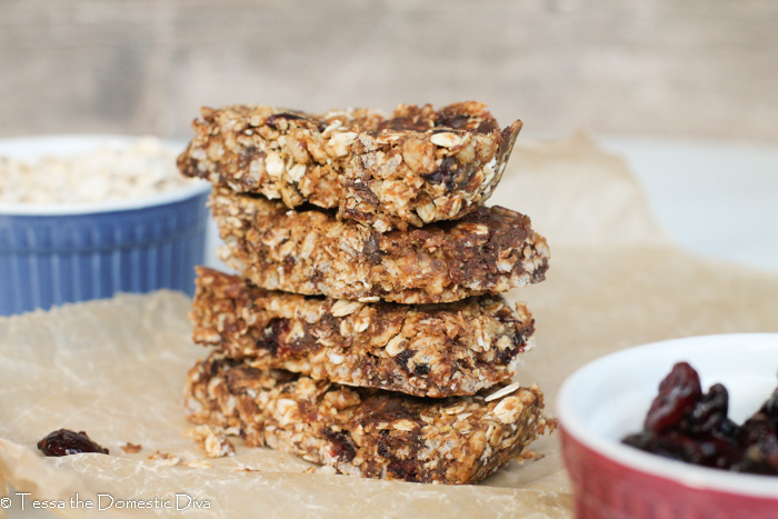 4 stacked rectangle granola bars with almond butter and cranberries.