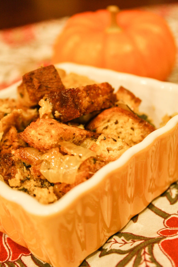 a square yellow ceramic baking dish with cubed bread cubes with onions, celery, and spices