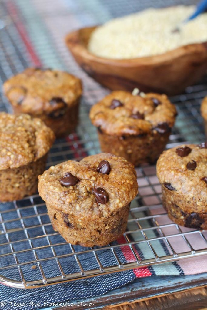 mini muffins with whole millet and chococlate chips on a coling rack with an olive wood bowl of millet grain in background