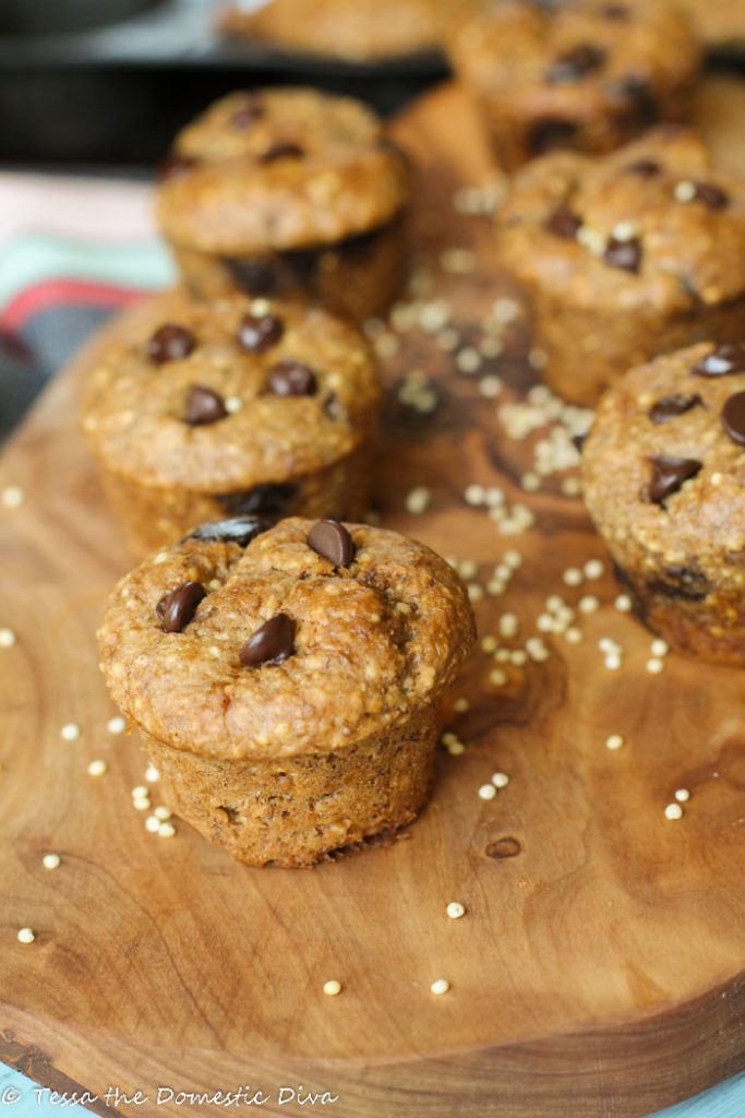 mini muffins studded with chococlate chips arranged on an olive wood cutting board with whole millet