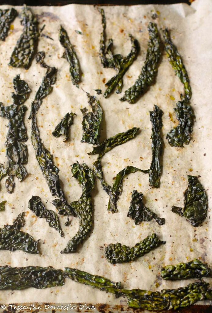 birds eye view of baked kale chips on unbleached parchment paper
