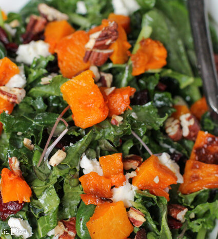 close up of a kale salad with cranberry, squash, and goat cheese