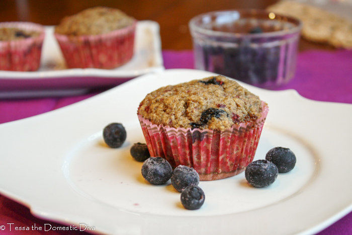 a wholegrain blueberry muffin studded with blueberries in a pink baking cup on a white plate with fresh blueberries scattered