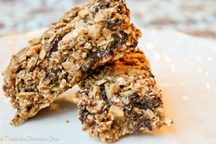 two cu rectangles of hmemade gluten fre granola bars with chocolate chips and raisins on a white plate
