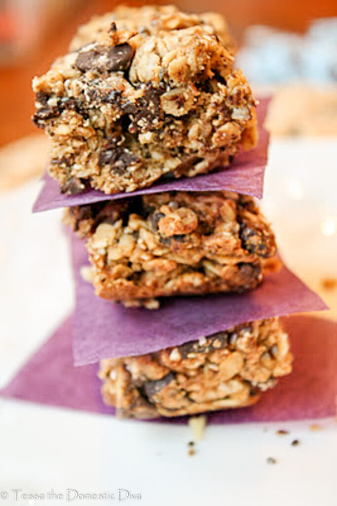 stack of three cut homemade granola bars with chococlate chips, raisins, and chia seeds