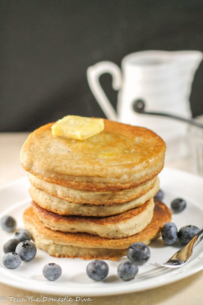 a stack of diner like pancakes with a pat of golden butter and fresh blueberries on a white plate with black background