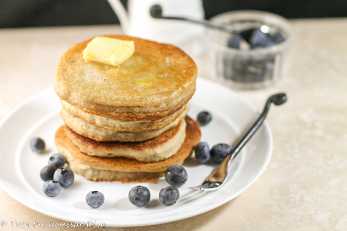 a stack of fresh golden pancakes with a pat of butter and fresh blueberries on a white plate