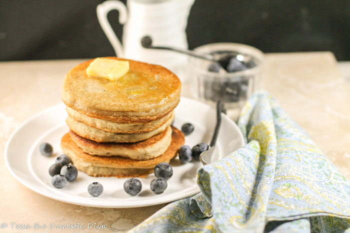 a stack of golden pancakes atop a white plate with a pat of golden butter and fresh blueberries with black background