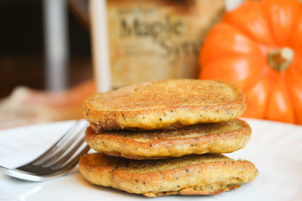 a horizontal image of three stacked golden orange pumpkin pancakes on a white plate with a fork