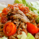 close up eye level view of tender shreds of pulled pork shoulder in a green chile sauce with cherry tomato halves atop butter lettuce