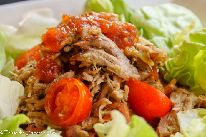 close up eye level view of tender shreds of pulled pork shoulder in a green chili sauce with cherry tomato halves atop butter lettuce