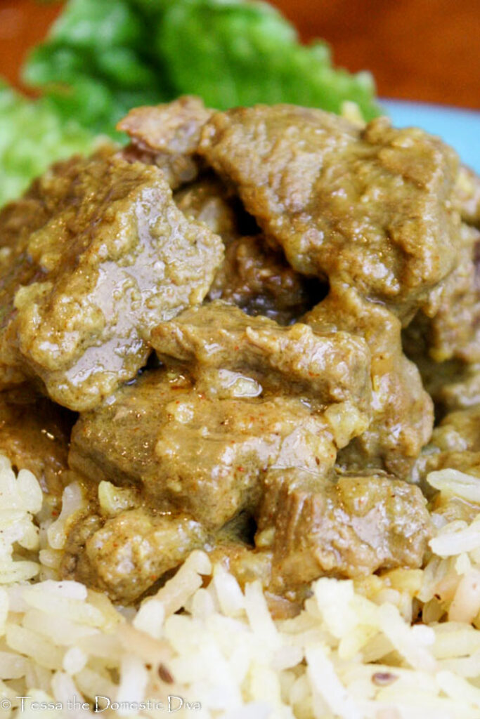 close up eye level of tender chuck roast cubes in an Indian sauce atop brown rice