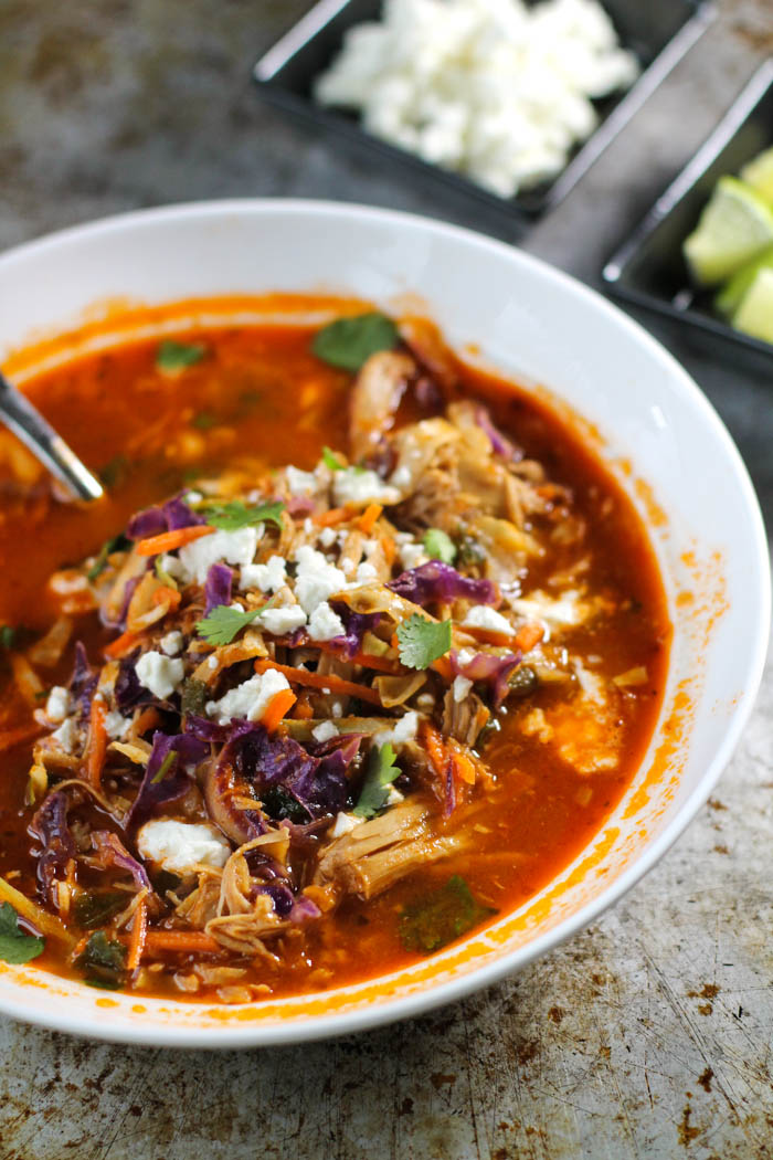 white bowl filled with a mexican flavored chicken and tomato soup with fresh cabbage and crumbled white feta cheese