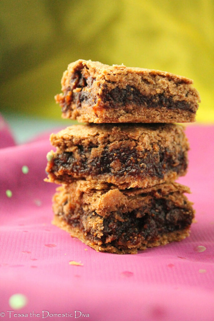 gluten free vegan fig newtons bars stacked on a sheer purple cloth