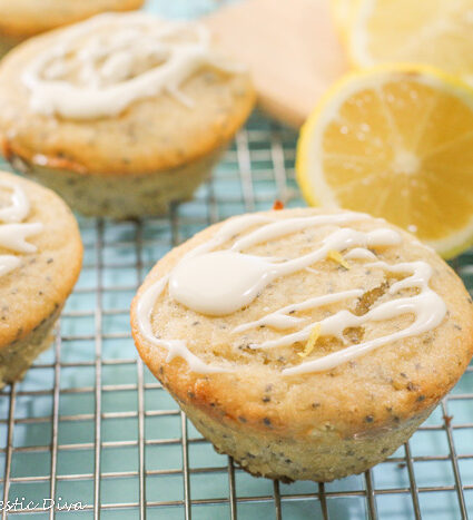 4 lemon poppy seed muffns topped with a creamy lemon glaze and grated lemon zest