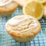 swirled lemon frosting atop a lemon poppy seed muffin with a sliced lemon half and pale turquoise cloth