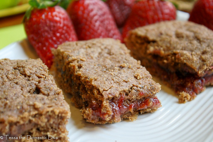 healthy homemade cereal bars with a strawberry filling on a white plate with fresh whole strawberries in the background