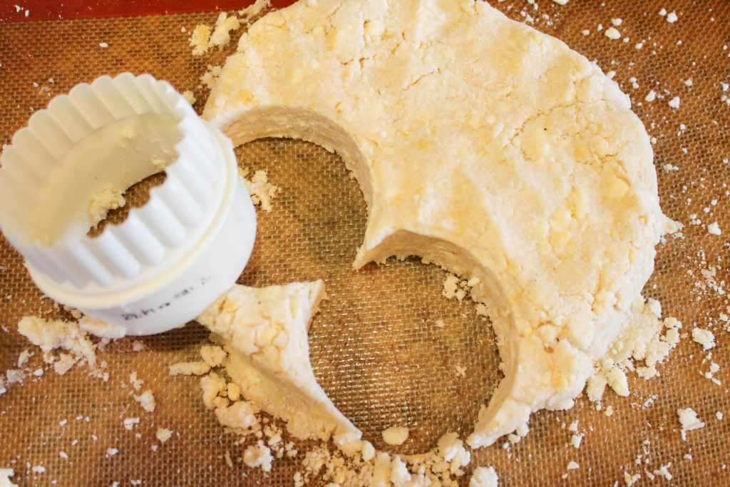 biscuit dough with cutter on a baking mat.
