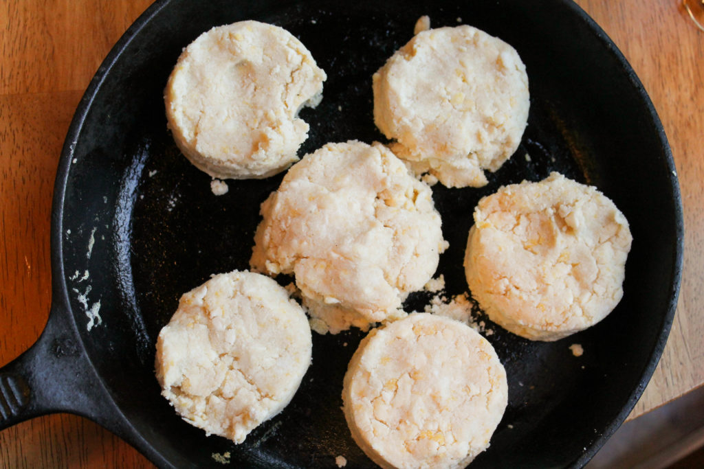 a cast iron pan with several cut biscuits ready to bake.