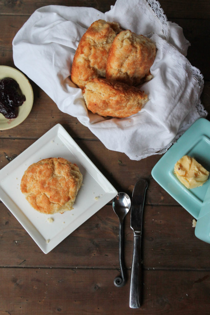 an arrange of golden biscuits on a dark wood surface with butter and jelly.