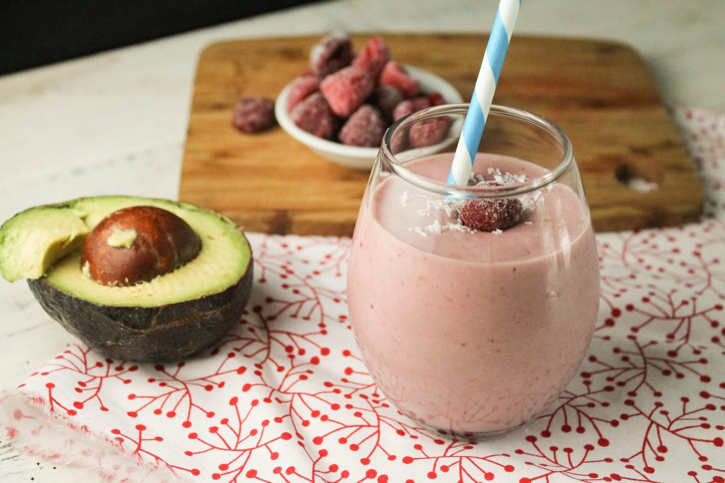 horizontal image of a pale pink raspberry smoothie in a clear glass with a blue and white paper straw, a halved avocado and a garnish of coconut flakes and frozen raspberries