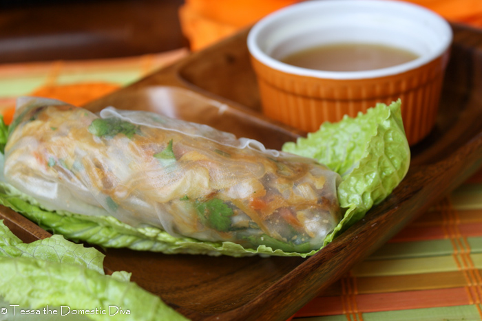 a single summer roll on a wooden plate with nuoc cham.