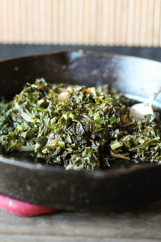 a black cast iron pan filled with chopped sauteed kale with caramelized onions