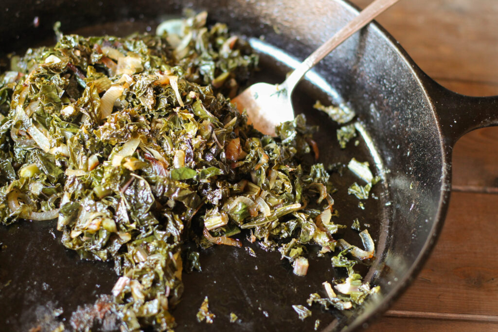 a silver serving fork in a black cast iron pan filled with sauteed kale and onions