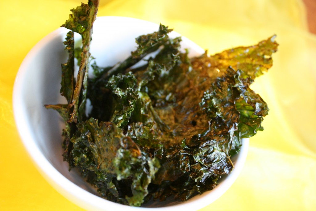 a white bowl filled with oven baked kale leaves from overhead on a bright yellow linen