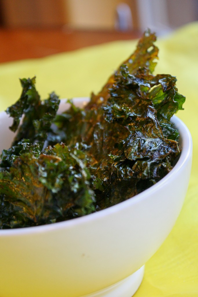 An eye level close up of a white bowl filled with crispy crunchy kale leaves