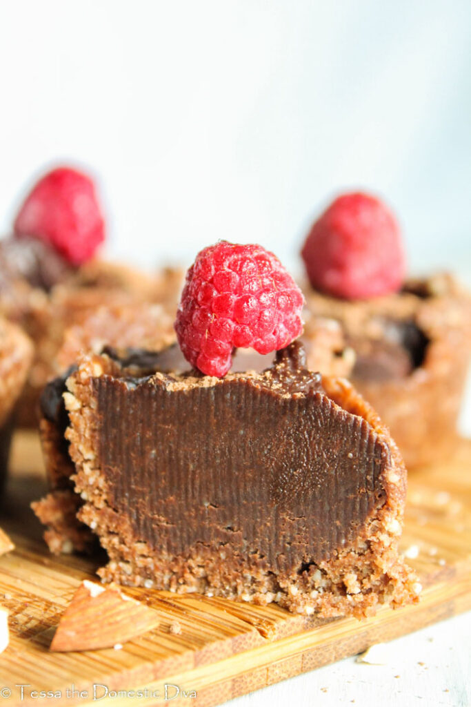 creamy chocolate cheesecake filling with a nut crust topped with a fresh raspberry and cut in half