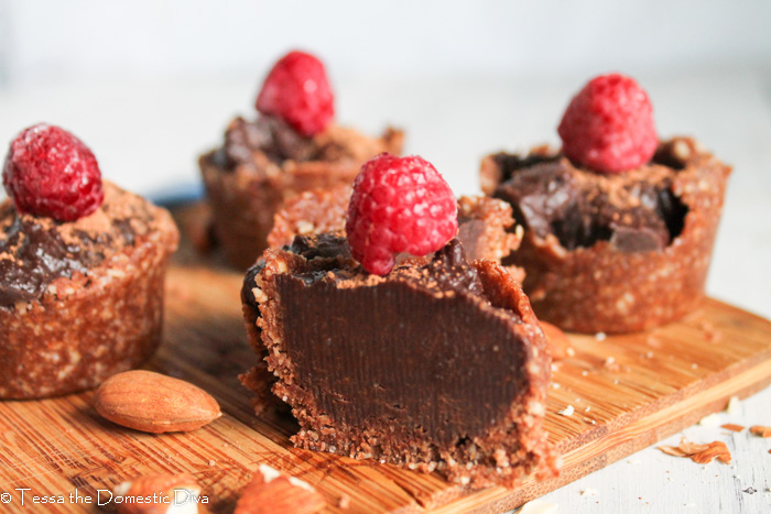 an arrangement of raw chocolate tarts topped with a raspberry atop a bamboo cutting board
