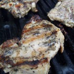 vertical image of peppered Vietnamese grilled chicken thighs on the grill