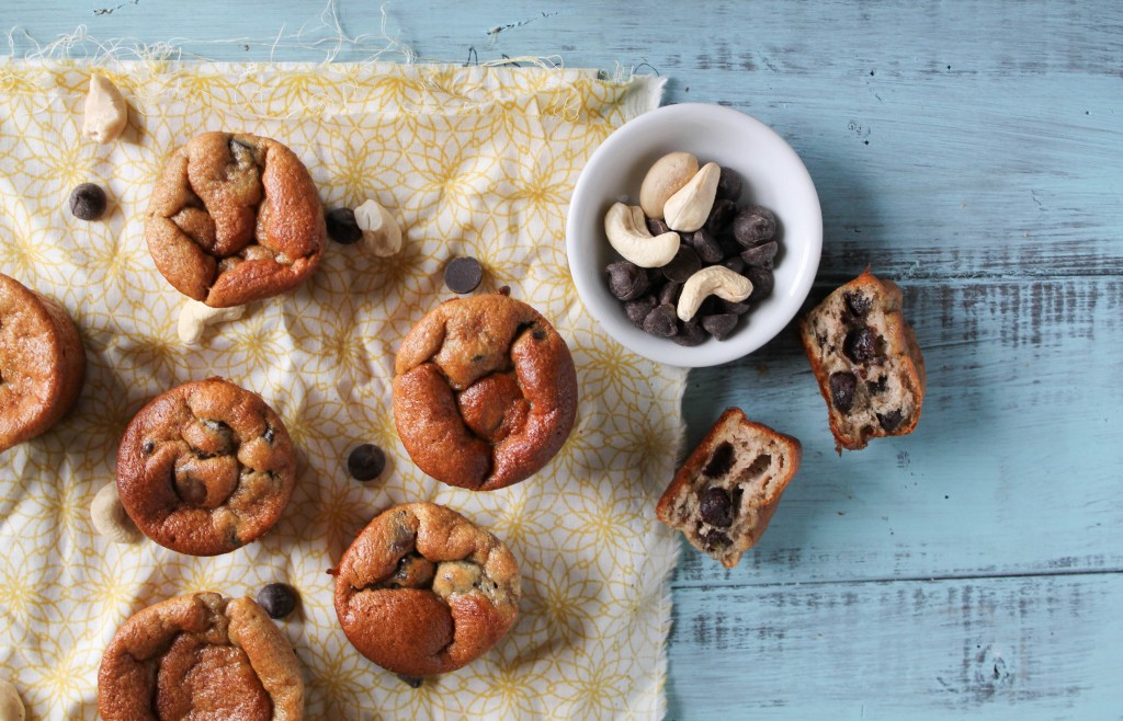 overhead shot of paleo mini banana muffins on a turquoise washed board with a bowl of chocolate chips and cashews