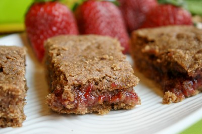 three rectangles of homemade fruit filled cereal bars with fresh strawberries on a white plate