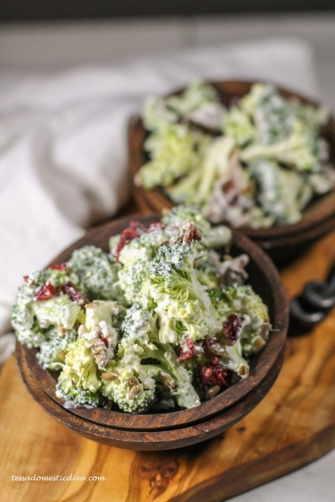 two deep brown wooden bowls filed with creamy broccoli bacon salad atop an olive wood cutting board