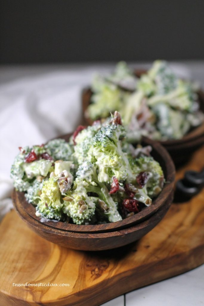 two wooden bowls filled with a creamy broccoli bacon salad with dots of bright red cranberries, aranged atop an live wood cutting board