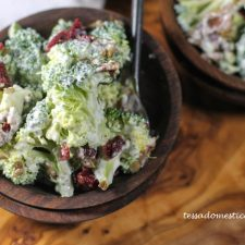 two olive wood bowls filled with a broccoli, bacon, and cranberry salad in a dairy free dressing