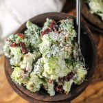 dark wooden bowls fillled with broccoli florets in a creamy sauce with chopped bacon, cranberries, and sunflower seeds